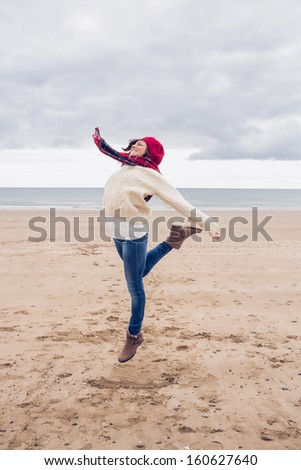 Full length of a woman in stylish warm clothing jumping at the beach