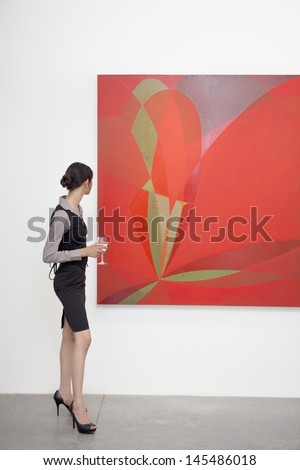 Full length of a woman looking at painting in art gallery - stock photo