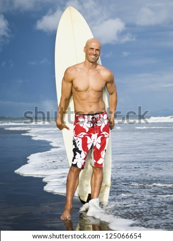 Full-length of a young bald man holding a surfboard on the beach - stock photo