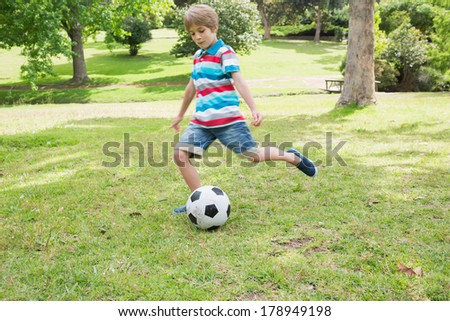 Full length of a young boy kicking ball at the park