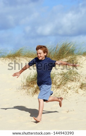 Full length of a young boy running down sand dune on beach - stock photo