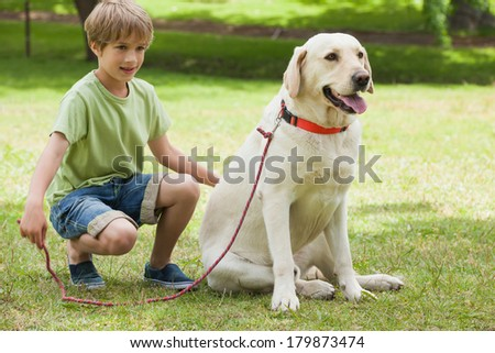 Full length of a young boy with pet dog at the park - stock photo