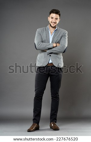 Full length of a young businessman on gray background - stock photo