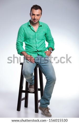 full length of a young casual man sitting on a high chair and holding a hand in his pocket. on gray background - stock photo