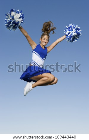 Full length of a young cheerleader jumping against clear sky - stock photo