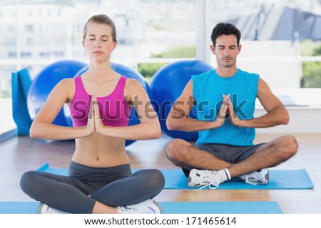 Full length of a young couple sitting with joined hands and eyes closed at fitness studio - stock photo