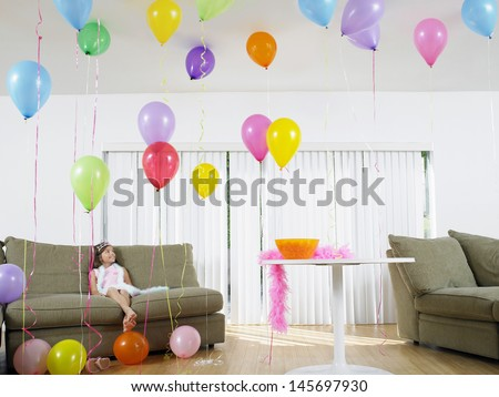 Full length of a young girl sitting in living room full of balloons - stock photo