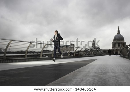 Full length of a young male runner with St Paul's in the background - stock photo