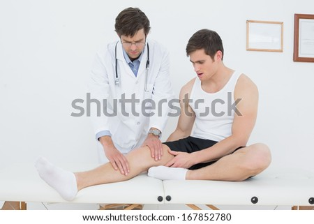 Full length of a young man getting his knee examined at the medical office - stock photo