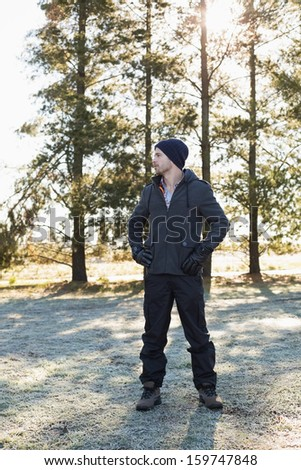 Full length of a young man in warm clothing while having a walk in forest on a winter day - stock photo