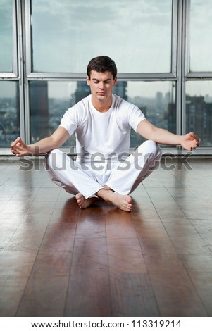 Full length of a young man meditating in lotus position at gym