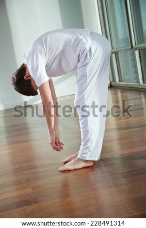 Full length of a young man practicing yoga called Standing Forward Bend at gym
