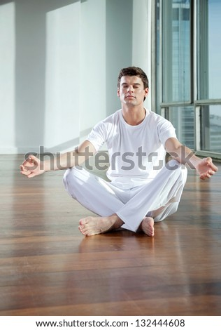 Full length of a young man practicing yoga in lotus position at gym
