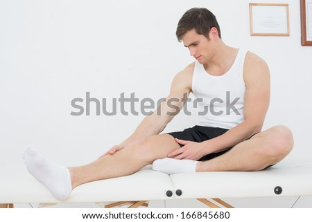Full length of a young man sitting on examination table in the medical office
