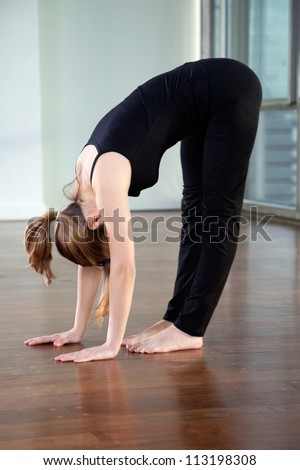 Full length of a young woman doing Standing Forward Bend in gym - stock photo