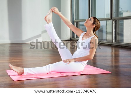 Full length of a young woman doing yoga exercise called Heron Pose at gym
