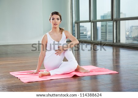 Full length of a young woman in Half Spinal Twist pose on mat - stock photo