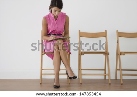 Full length of a young woman in pink dress writing at waiting room - stock photo