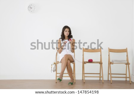 Full length of a young woman in white dress knitting in waiting room - stock photo