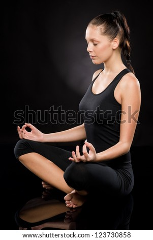 Full length of a young woman meditating with eyes closed - stock photo