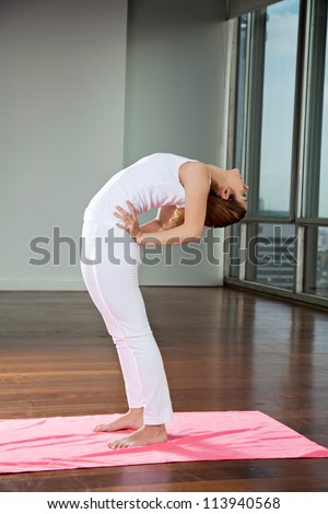 Full length of a young woman practicing yoga and making backbend at gym - stock photo