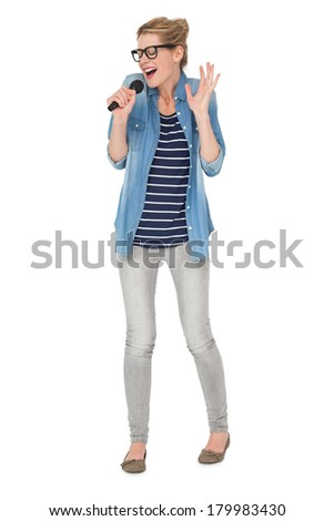 Full length of a young woman singing into a microphone over white background - stock photo