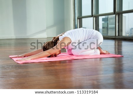 Full length of a young woman sitting in child's pose on a yoga mat - stock photo