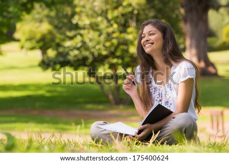 Full length of a young woman with book and pen sitting in the park