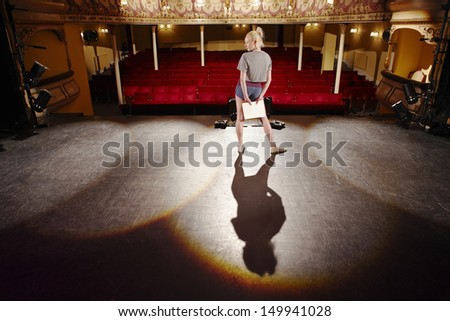 Full length of a young woman with script rehearsing on stage - stock photo