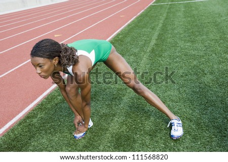 Full length of African American female athlete stretching on track and field - stock photo