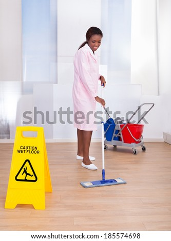 Full length of African American female housekeeper cleaning floor in hotel - stock photo