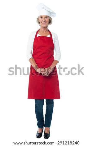 Full length of aged woman chef with hands clasped