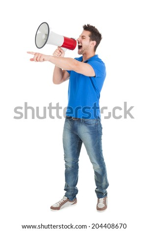 Full length of aggressive young man screaming into bullhorn while pointing away over white background - stock photo