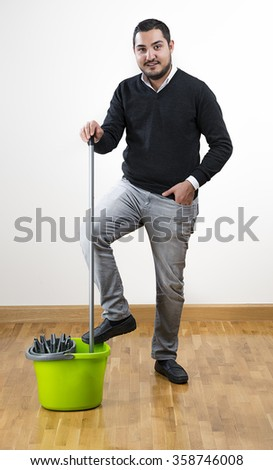 Full length of an adult man mopping floor at home.     - stock photo