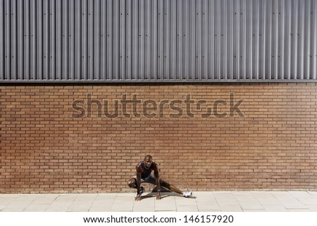 Full length of an African American man stretching against brick wall - stock photo