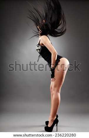 Full length of an exotic dancer in black costume dancing, flipping her hair - stock photo