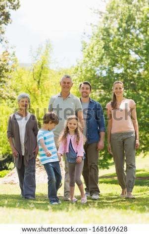 Full length of an extended family walking in the park - stock photo
