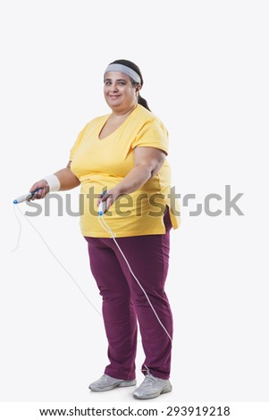 Full length of an overweight female with skipping rope over white background - stock photo
