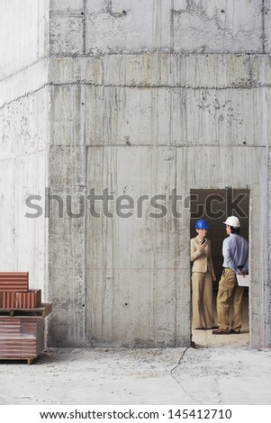 Full length of architect and construction manager discussing at site - stock photo