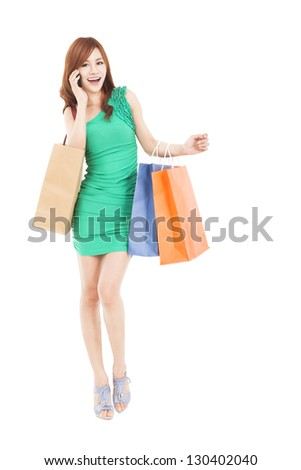 full length of asian woman with shopping bags talking on the phone - stock photo