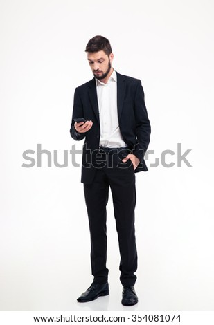 Full length of attractive confident young bearded businessman  in black suit using mobile phone over white background - stock photo