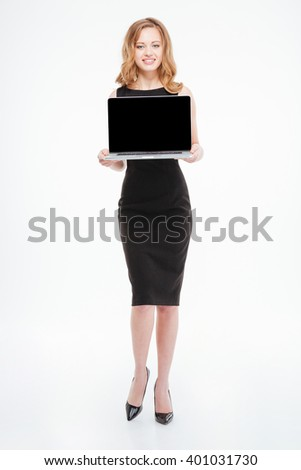 Full length of attractive smiling young businesswoman standing and holding blank screen laptop over white background  - stock photo
