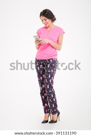 Full length of attractive smiling young woman standing and using mobile phone over white background - stock photo