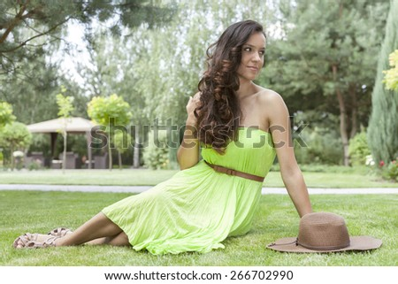 Full length of attractive young woman in sundress at park - stock photo