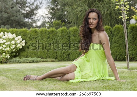 Full length of attractive young woman in sundress relaxing at park - stock photo