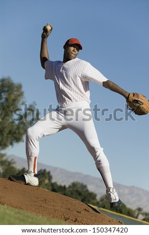 Full length of baseball pitcher throwing ball during game - stock photo