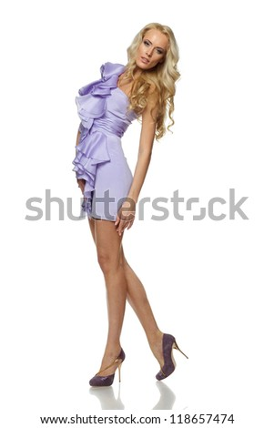 Full length of beautiful blond female standing in lilac dress over white background