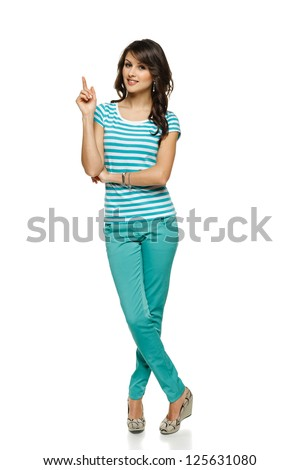 Full length of beautiful blond woman pointing up at copy space over white background - stock photo