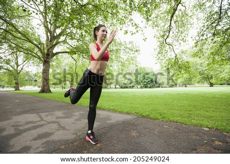 Full length of beautiful fit woman jogging in park