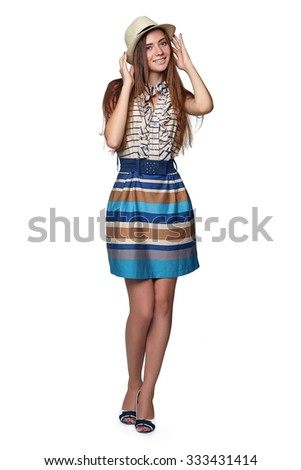 Full length of beautiful girl posing  in summer dress and a hat, over white background.
